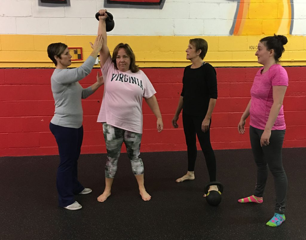 helping a client with proper kettlebell form